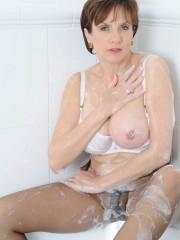 Busty MILF Sonia taking a bath in her sheer brown pantyhose